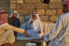 Arabic men drinking coffee. Arabic men in dishdashah sitting on rugs drinking coffee Stock Image