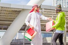 Arabic men shopping. Happy Arabic men with city shopping hand holding paper bags royalty free stock photography