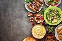 Arabic and Middle Eastern dinner table. Hummus, tabbouleh salad, Fattoush salad, pita, meat kebab, falafel, baklava, pomegranate.
