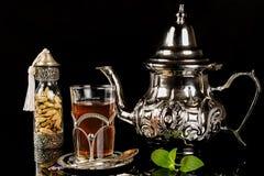 Arabic mint tea and cardamon seeds. On the black background Stock Photos