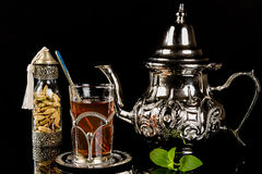Arabic mint tea and cardamon seeds. On the black background Stock Images