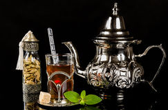 Arabic mint tea and cardamon seeds. On the black background Stock Photography