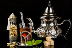 Arabic mint tea and cardamon seeds. On the black background Royalty Free Stock Photography