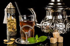 Arabic mint tea and cardamon seeds. On the black background Stock Photo