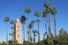 Arabic mosque minaret among the palm trees. Arabic mosque in Marakkesh, Morocco. Mosaic decoration on the wall. Main square in Marakkesh, palm trees park. Arabic stock image