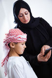 Arabic mother and her son using smart phone Royalty Free Stock Image