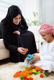 Arabic mother and son together at home playing with toys. Stock Photography