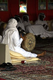 Arabic Musician. Arabic musical instruments being played by man in traditional clothing, sitting in a room before three other men in similar dress Stock Photography