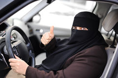 Arabic Muslim woman driving a car. With thumb up Royalty Free Stock Images