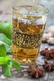 Arabic nana mint tea in traditional glass with mint, cinnamon, anise stars on a old white wooden board. Arabic nana mint tea in traditional glass with mint Royalty Free Stock Photo