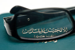 Arabic New Testament. Close-up of Arabic New Testament with reading glasses royalty free stock image