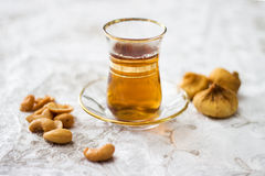 Arabic, oriental tea with cashew and dry figs. On white background Royalty Free Stock Photography