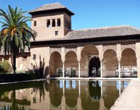 Arabic palace with decorative pool and palm. This post-islamic palace - part of Alhambra fortress (Granada, Spain) is now world known museum Stock Photos