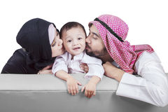 Arabic parents kiss their son. Photo of two Arabian parents kissing their son while sitting on the sofa Stock Photography