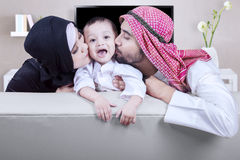 Arabic parents kissing their son cheek at home. Two young Arabic parents kissing their son cheek while sitting on the sofa at home Stock Images