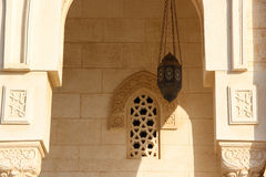 Arabic Patterned narrow window on an old stone wall with an ancient lamp hanging near, Egypt Stock Photos