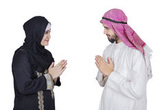 Arabic people with hand gesture. Arabic women giving a greeting hand gesture at the Arabic man, isolated on white background Royalty Free Stock Images