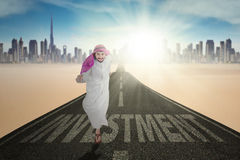 Arabic person and text of Investment at road. Arabic businessman running on the road with text of Investment and wearing islamic clothes Royalty Free Stock Image