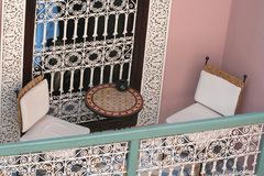 Arabic residential balcony. Arabic stylish balcony with two chairs, table and ornate window Royalty Free Stock Photography