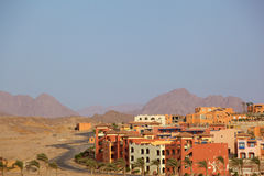 Arabic rural town. Horizontal picture of Arabic rural town in the desert, winding road, the mountains on the horizon and the blue clear sky. A lot of empty space Stock Photo