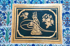 Arabic script, named tughra, in a Ottoman tiles.  Topkapi Palace, Istanbul, Turkey. Royalty Free Stock Photo