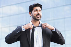 Angry businessman or worker standing in suit and straightening tie royalty free stock image