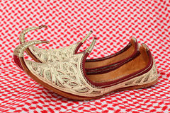Arabic shoes. Traditional oriental shoes over arabic cloth Royalty Free Stock Photos