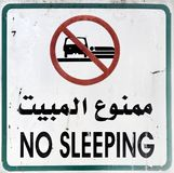 Arabic sign with the inscription & x22;No sleeping& x22; to forbid sleeping in a car on the beach of Aqaba, Jordan Royalty Free Stock Photos