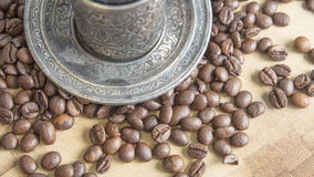 Arabic silver coffee cup with raw beans Royalty Free Stock Photos