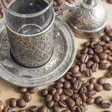 Arabic silver coffee cup with raw beans Royalty Free Stock Images