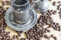 Arabic silver coffee cup with raw beans Stock Photo