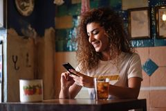 Arabic smiling woman in a beautiful bar looking at her smartphon. Young arabic woman with black curly hairstyle sitting in a beautiful bar with vintage Stock Photos