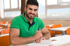 Arabic Student With Books Sitting In Classroom. Portrait Of Young Arabic Male College Student With Book Sitting In Classroom Alone Royalty Free Stock Image