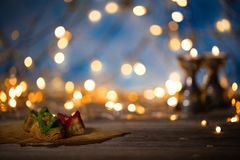 Arabic sweets on a wooden surface. Candle holders, night light and night blue sky with crescent moon in the background Royalty Free Stock Photo