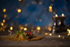 Arabic sweets on a wooden surface. Candle holders, night light and night blue sky with crescent moon in the background Stock Images