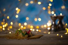 Arabic sweets on a wooden surface. Candle holders, night light and night blue sky with crescent moon in the background Royalty Free Stock Image