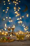 Arabic sweets on a wooden surface. Candle holders, night light and night blue sky with crescent moon in the background Stock Photography