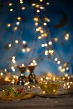 Arabic sweets on a wooden surface. Candle holders, night light and night blue sky with crescent moon in the background Stock Image