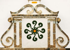 Arabic symbol & decorative details. Andalusia. Arabic symbol - similar to the sign of The Sun also to the swastika placed between decorative reliefs. Competa Royalty Free Stock Photography