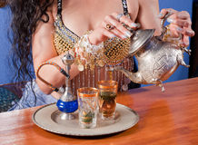 Arabic tea. Woman in traditional costume pouring fresh green tea Royalty Free Stock Photo