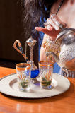 Arabic tea. Woman in traditional costume pouring fresh green tea Stock Images