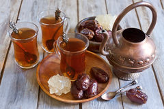 Arabic tea and dates. Traditional arabic tea with dry madjool dates and rock sugar nabot. Selective focus Stock Photography