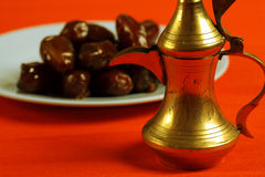 Arabic teapot and dates. In the background Stock Image