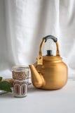 Arabic teapot on white wooden table. Arabian golden teapot on white wooden table Stock Photo