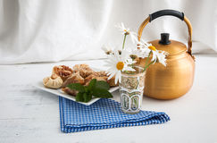 Arabic teapot on white wooden table. Arabian golden teapot on white wooden table Royalty Free Stock Image