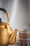Arabic teapot on white wooden table. Arabian golden teapot on white wooden table Royalty Free Stock Images