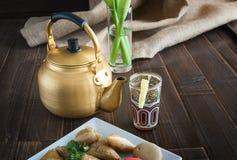 Arabic teapot on white wooden table. Arabian golden teapot on white wooden table Stock Image