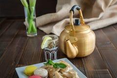 Arabic teapot on white wooden table. Arabian golden teapot on white wooden table Royalty Free Stock Photo