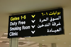 Arabic text. Doha International Airport in Qatar. Departure gates, duty free shop, smoking room and clinic - illuminated sign in English and Arabic Stock Photos