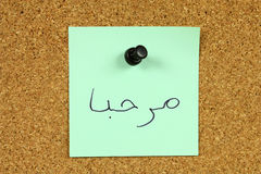 Arabic text. Green small sticky note on an office cork bulletin board. Word marhaba in Arabic, which means hi or hello Royalty Free Stock Image
